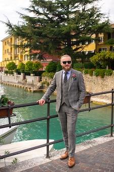 シルミオーネの旧市街で、ネクタイをした厳格なグレーのスリーピーススーツを着たあごひげを生やした男性。