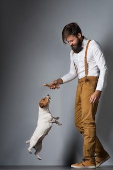 白いシャツにひげを生やし、灰色の背景にペットの犬ジャックラッセルテリアと遊んでいる黄色のサスペンダーを持つ男
