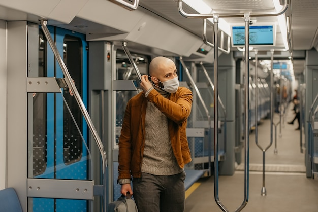あごひげを生やした男性が、地下鉄の車内でのコロナウイルスの蔓延を防ぐために医療用フェイスマスクを着用しています。 covid-19に対するサージカルマスクのハゲ男が電車の中で社会的距離を保っています。