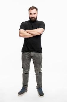 あごひげを生やした男が立っており、腕を胸に組んでいる。ジーンズと黒のtシャツの若い男。フルハイト。白色の背景。垂直。