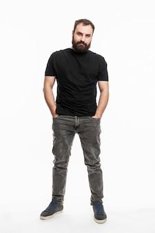 수염을 기른 남자가 주머니에 손을 넣고 서 있습니다. 청바지와 검은색 티셔츠를 입은 청년. 전체 높이. 흰 바탕. 수직의.