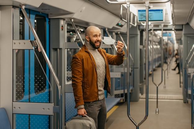 あごひげを生やした男性が、医療用フェイスマスクを脱いで、地下鉄の車の中で笑っています。 covid-19に対するサージカルマスクを持ったハゲ男が電車の中で社会的距離を保っています。