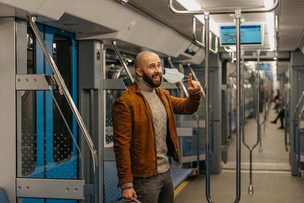 あごひげを生やした男性が、医療用フェイスマスクを脱いで、地下鉄の車の中で笑っています。サージカルマスクを持ったハゲ男が電車の中で社会的距離を保っています。