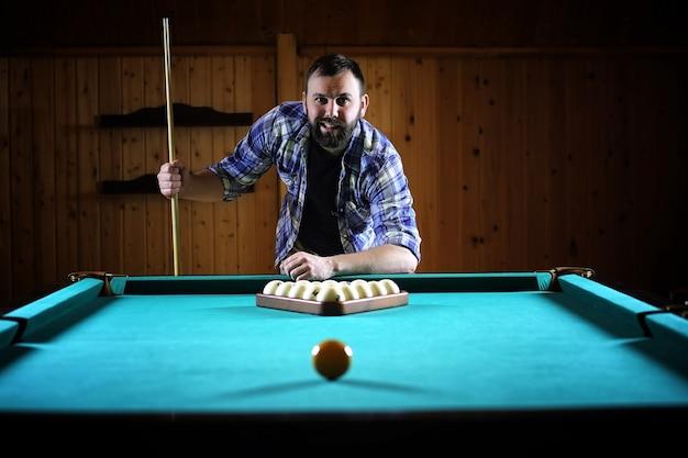 あごひげを生やした男が大きなビリヤードをします。 12フィートのプールでのパーティー。男性のためのクラブゲームのビリヤード。手がかりを持った男がピラミッドを壊します。