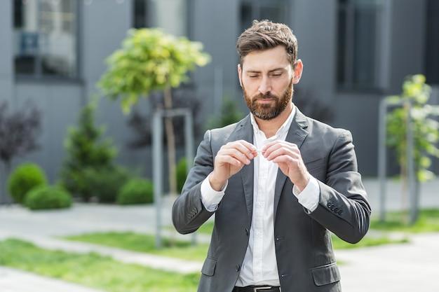 あごひげを生やした男性がタバコの喫煙をやめ、手でタバコを壊し、喫煙と戦う