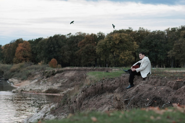 Человек с книгой в руках сидит на краю обрыва и выглядит задумчивым Premium Фотографии