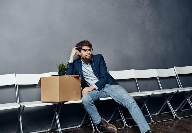 상자를 든 남자가 의자에 앉는다.
