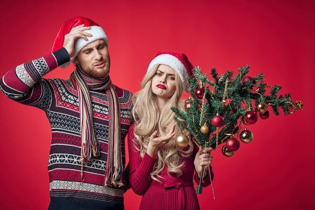 女性の感情の休日の装飾の横に彼の手でクリスマスツリーを持つ男