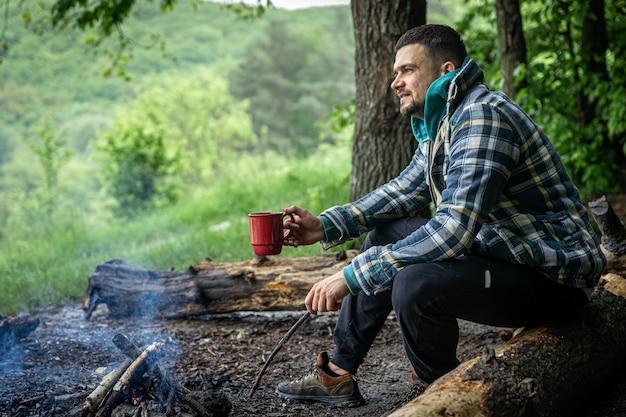 Мужчина с чашкой согревающего напитка греется у костра в лесу.