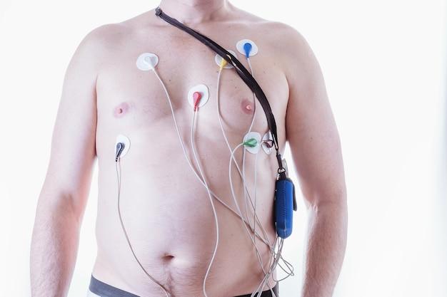밝은 배경에서 심전도를 매일 측정하는 장치를 가진 남자. 고삐의 방법. 심장병 진단 방법.
