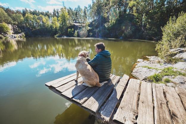 Мужчина с собакой сидит на деревянной террасе на красивом каменистом берегу озера