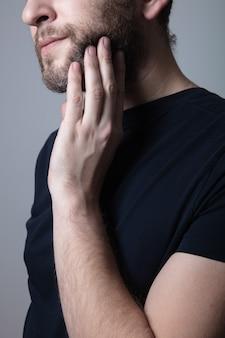 회색 수염을 가진 남자는 그의 뺨에 가려움증과 발진을 앓고 있습니다. 알레르기 반응, 습진 개념. 회색 수염 문제 개념