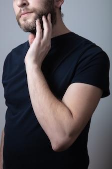 灰色のあごひげを生やした男性は、灰色の背景に立っている頬のかゆみと発疹に苦しんでいます。アレルギー反応、湿疹の概念。灰色のひげの問題の概念
