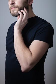 灰色のあごひげを生やした男性は、灰色の背景に立っている頬のかゆみと発疹に苦しんでいます。アレルギー反応。湿疹の概念。灰色のひげの問題の概念