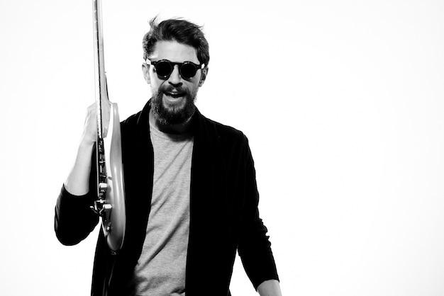 Мужчина с гитарой эмоции музыка игра выступление кожаная куртка солнцезащитные очки светлый фон