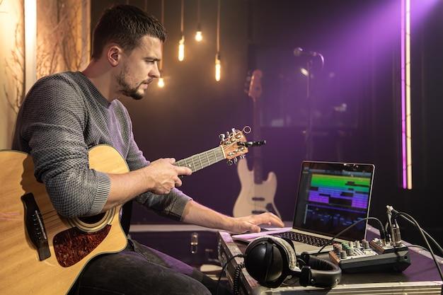 기타를 가진 남자가 자신의 노트북에 특수 프로그램을 사용하여 음악 스튜디오에서 사운드를 녹음합니다.