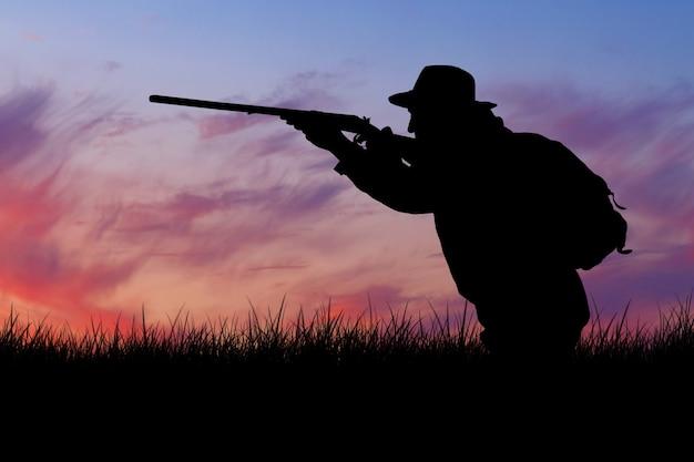 手に銃を持ち、森の中でキジ狩りをしている緑のベストを持った男