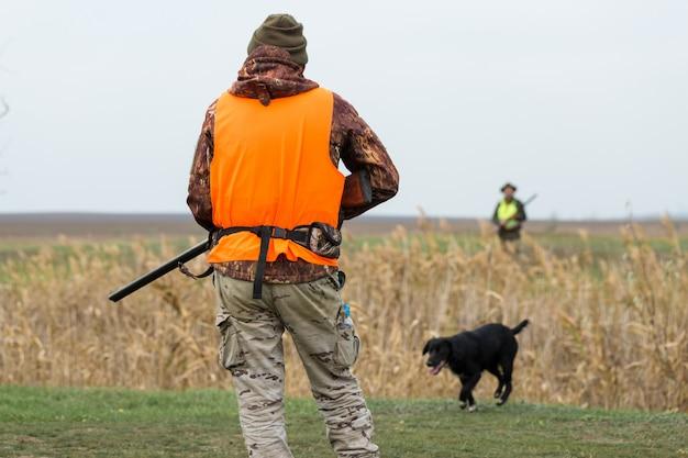 Человек с пистолетом в руках и оранжевым жилетом на охоте на фазана в лесистой местности в пасмурную погоду.