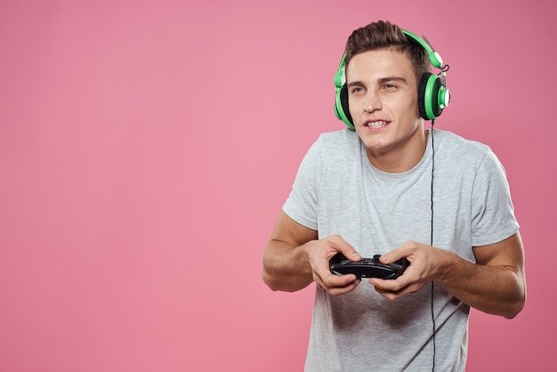 그의 손에 헤드폰 게임 엔터테인먼트 라이프 스타일 흰색 t- 셔츠 핑크 벽에 조이스틱을 가진 남자.