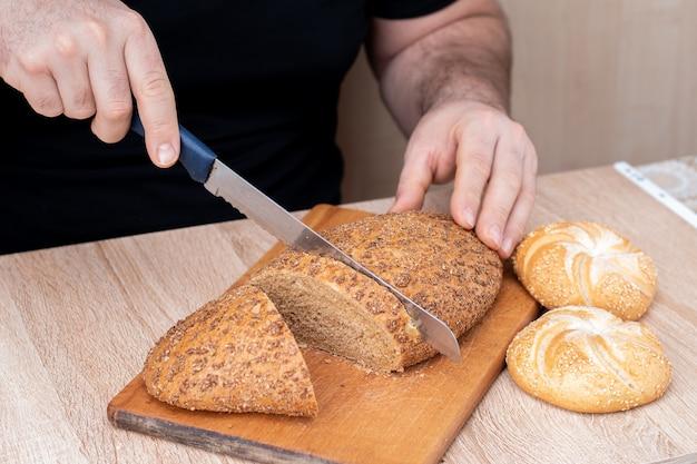 칼을 가진 남자는 나무 보드에 빵을 자른다. 프랑스 바게트. 나무 배경에 다른 품종.