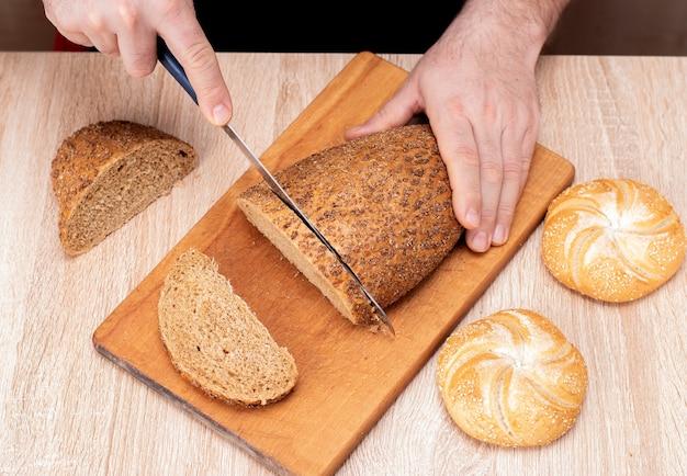 Мужчина ножом режет хлеб на деревянной доске. французские багеты. разные породы на деревянных фоне.