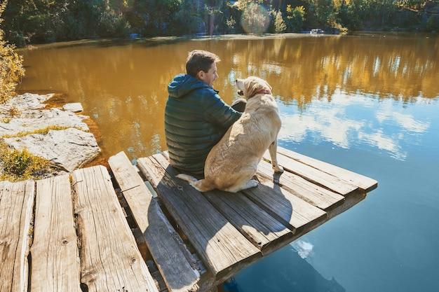 Мужчина с собакой лабрадора-ретривера сидит на деревянной террасе на скалистом берегу озера.