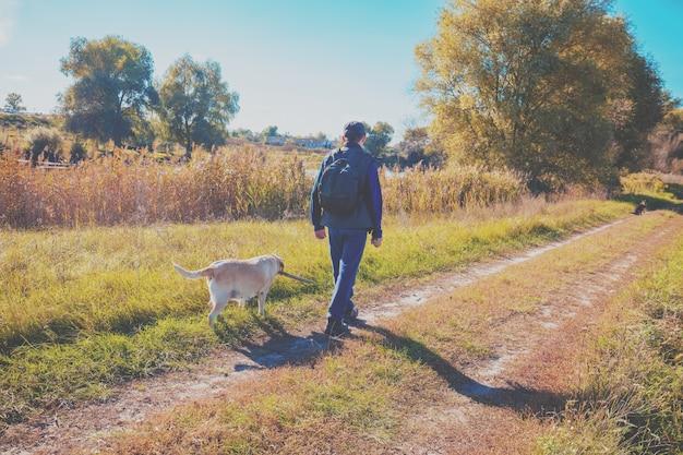 Мужчина с собакой лабрадора-ретривера гуляет по сельской дороге осенью