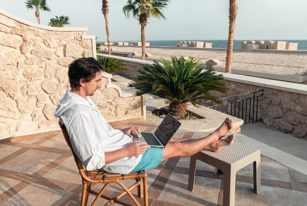 ノートパソコンを手に持った男性が、ヤシの木のテーブルでフリーランサーとして休んで働いています。