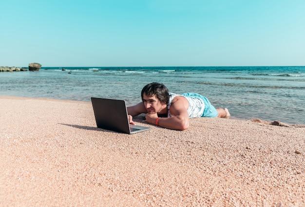 Мужчина с ноутбуком на песке отдыхает и работает фрилансером