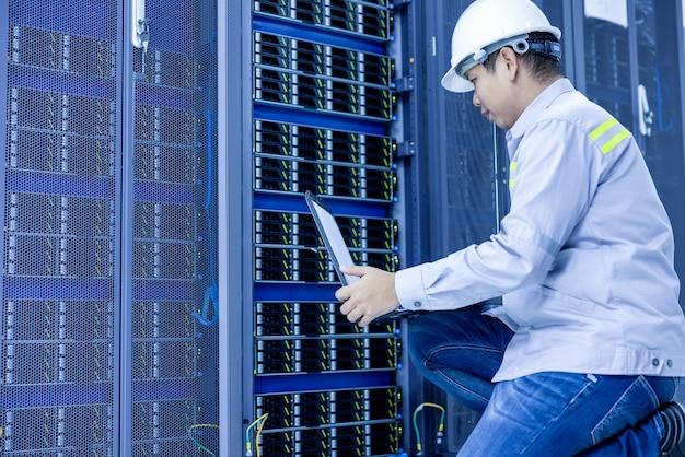 ラップトップを持った男性がデータセンターのサーバールームに座っています。システム管理者は、サーバーのあるラックの近くで作業します。
