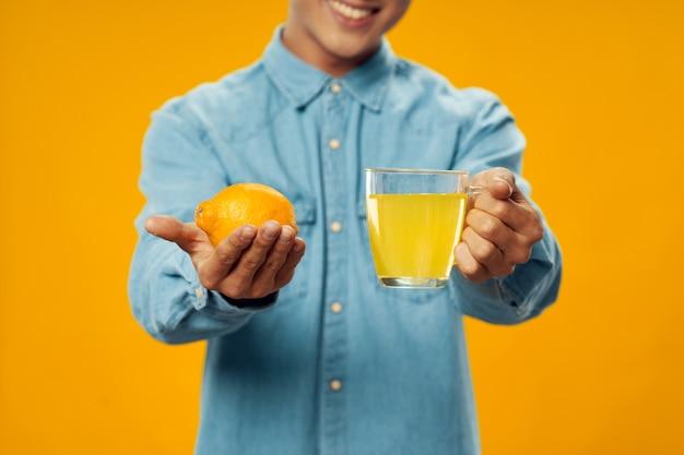 レモンを手に持ち、カップに飲み物を飲む男性
