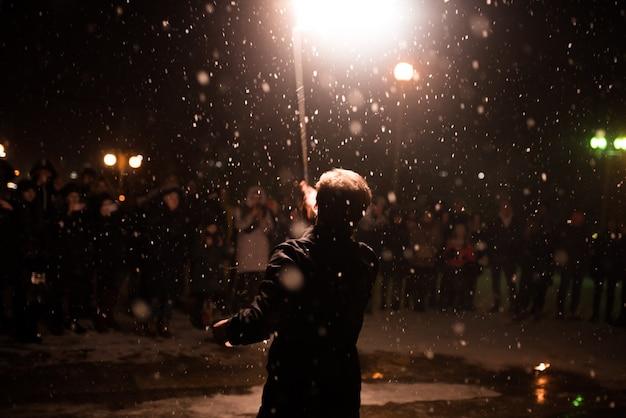 Мужчина с зажженным факелом над головой огненное шоу