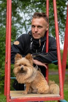 Мужчина с собачкой на качелях. для любых целей.
