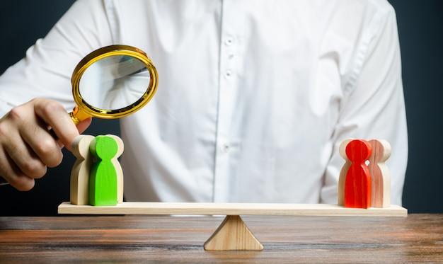 Человек с увеличительным стеклом смотрит на конкурирующие красные и зеленые фигуры групп на весах