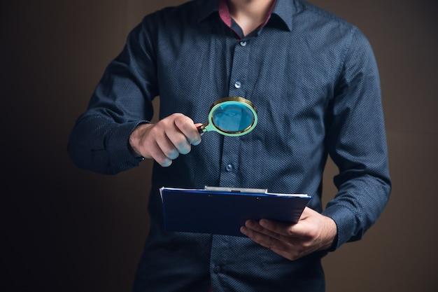 돋보기를 가진 남자는 갈색 표면에 서류를 본다