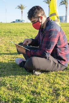 Мужчина в маске сидит на траве с планшетом и электросамокатом позади него в пальма-де-майорка, испания (по вертикали)
