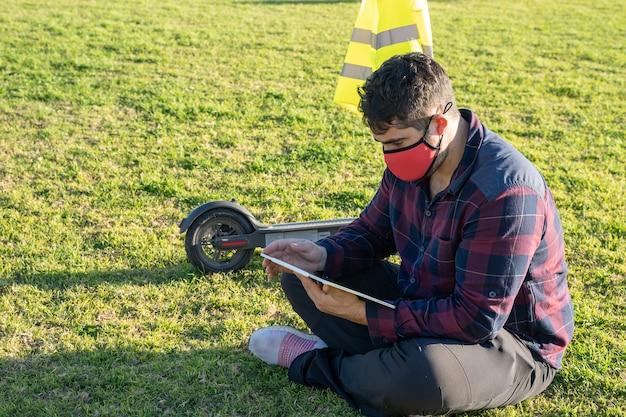 Мужчина в маске сидит на траве с планшетом и электросамокатом позади него в пальма-де-майорка, испания.