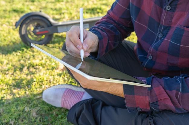 Мужчина в маске сидит на траве с планшетом со стилусом и электросамокатом позади него в пальма-де-майорка, испания.