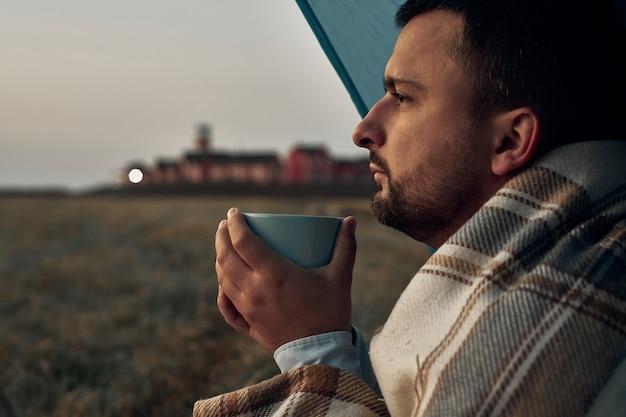 マグカップを手にした男が夜明けを見る。灯台と背景の建物。旅行、自然の中での日の出。