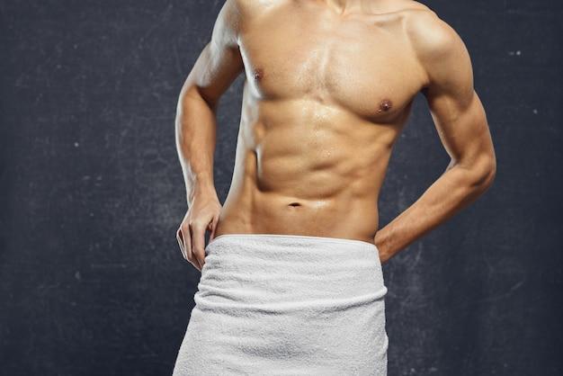 裸のポンプアップされた胴体を持つ男は、タオルフィットネスボディービルダーで身を覆います
