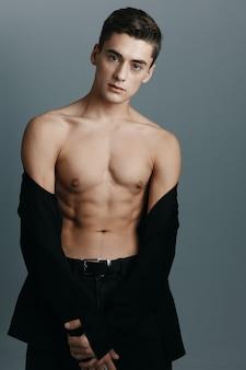 벗은 몸통과 바지에 단추가없는 재킷을 입은 남자가 모델입니다.
