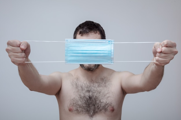 裸の胴体を持った男性は、顔の前に医療用保護マスクをかぶせて、顔に激しい刺激を隠します。