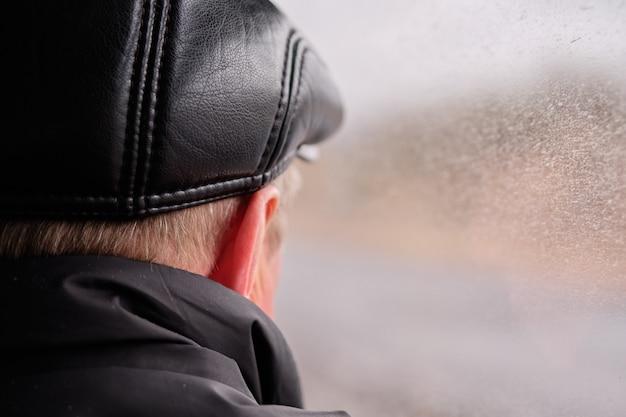 가죽 모자에 목덜미가있는 사람이 안개가 자욱한 창에서 보입니다.