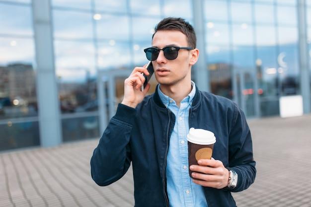 コーヒーの紙コップを持った男が街を通り抜け、スタイリッシュな服とサングラスをかけたハンサムな男が電話をかける