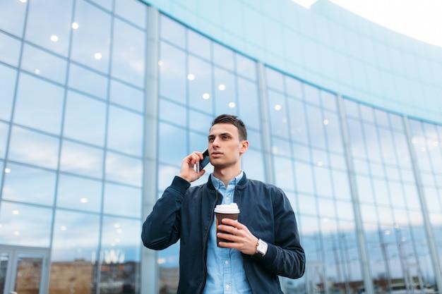 コーヒーの紙コップを持つ男は、電話でスタイリッシュな服を着たハンサムな男、街を通り抜けます