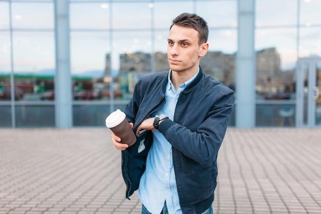 コーヒーの紙コップを持った男が街を通り抜け、スタイリッシュな服を着たハンサムな男がポケットから電話を引き出します