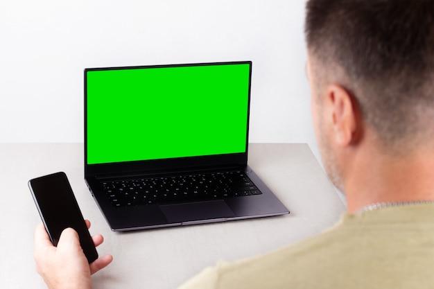 손에 전화기를 들고 있는 남자가 녹색 모니터가 있는 노트북 앞에 앉아 있다