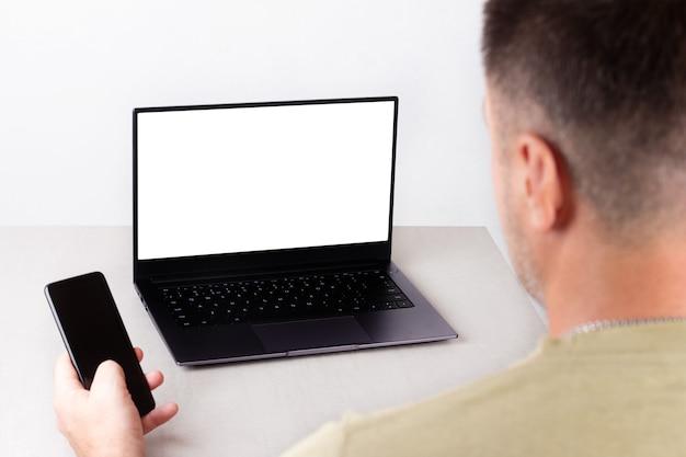 손에 전화기를 들고 있는 한 남자가 모니터에 흰색 모형이 있는 노트북 앞에 앉아 있고, 사무, 원격 작업, 마케팅, 교육, 코칭의 개념입니다.