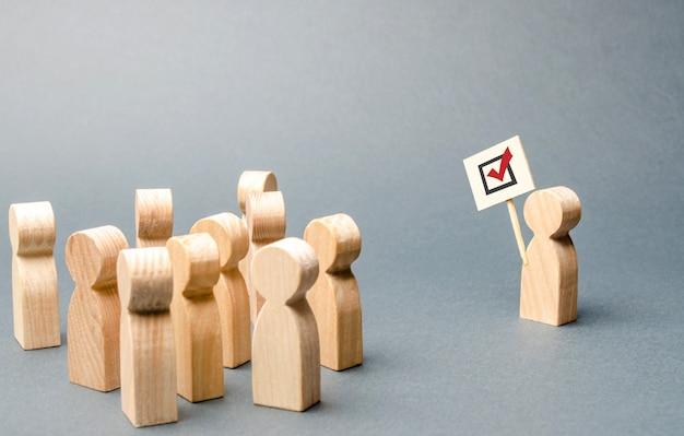 Человек с плакатом волнует группу людей. агитация, референдум, опрос