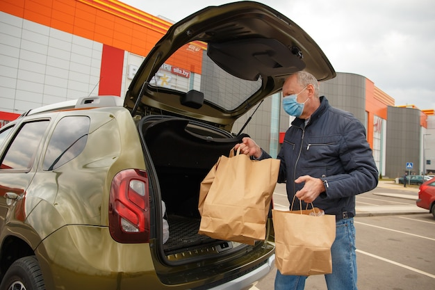 얼굴에 보호 마스크를 쓴 남자가 식품 포장을 차에 싣는다